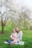 Mother and daughter sitting under spring tree Stock Photography