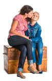 Mother and daughter sitting on a wooden chest Royalty Free Stock Images