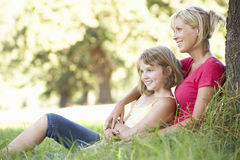 Mother And Daughter Sketching In Countryside Leaning Against Tree Royalty Free Stock Photography