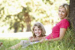 Mother And Daughter Sketching In Countryside Leaning Against Tree Royalty Free Stock Images