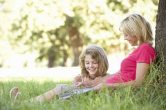 Mother And Daughter Sketching In Countryside Leaning Against Tree Royalty Free Stock Photos