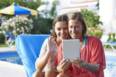 Mother and Daughter Skpying On Digital Tablet. Mother and Daughter keeping in touch with friends and family using a digital tablet while on holiday royalty free stock images