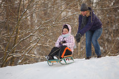 Mother and daughter sledging Royalty Free Stock Images