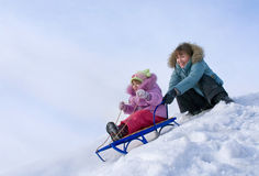 Mother and daughter sledging Stock Photos