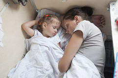Mother and daughter sleeping on a cot in back of train Royalty Free Stock Photos