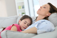 Mother and daughter sleeping on a sofa stock images