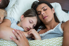 Mother and daughter sleeping together in bedroom Stock Photography