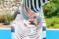 Mother and daughter sliding in aquapark Stock Images