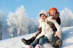 Mother and daughter sliding in the snow Stock Images