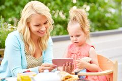 Mother and daughter with smartphone at cafe Stock Photography