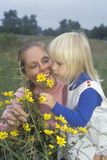 A mother and daughter smelling wildflowers Stock Images