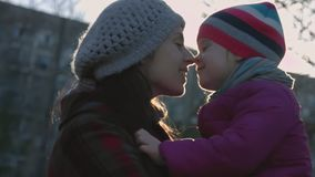 Mother and daughter smile while looking into one another`s eyes. Horizontal shot. Family concept. Happy childhood. Concept. Slow motion stock footage