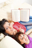 Mother and daughter smile while reading a book Stock Image