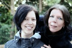 Mother and daughter smiling. Mother and daughter, outdoor, closed together, close-up, smiling and looking royalty free stock images