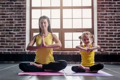 Mother and daughter smiling while doing yoga exercises sitting in Padmasana relaxing on mat at home.  Royalty Free Stock Images