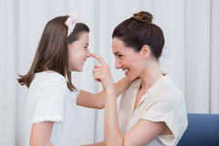 Mother and daughter smiling at each other Stock Images