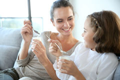 Mother and daughter smiling and eating yoghurt Royalty Free Stock Photos