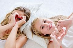 Mother and daughter making heart shape from hand while lying on bed at home Stock Images