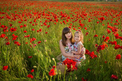 Mother and daughter smiling in a poppy field. The Picnic in the poppy field. Walk with family in poppy field. The cart poppies Royalty Free Stock Image