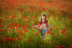 Mother and daughter smiling in a poppy field. The Picnic in the poppy field. Walk with family in poppy field. The cart poppies Stock Image