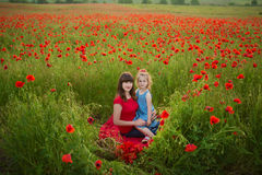 Mother and daughter smiling in a poppy field. The Picnic in the poppy field. Walk with family in poppy field. The cart poppies Royalty Free Stock Images