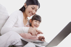 Mother and daughter smiling and sitting close together on the sofa, using and pointing at the laptop, tilt Royalty Free Stock Photos