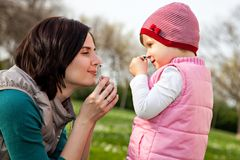 Mother and daughter sniffing flowers in park Royalty Free Stock Images