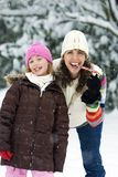 Mother and Daughter in the Snow. A Mother and Daughter eating Candy Canes in the snow Stock Images