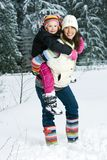 Mother and Daughter in the snow. A pretty Mom with colorful striped boots carrying her cute daughter on her back.  They are walking in deep, white snow Stock Photos
