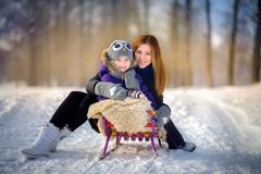 Mother with the daughter in the snow wood stock images