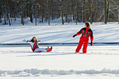 Mother and daughter in snowy winter park. Middle aged women pulling red sledge with her daughter across a snow field Royalty Free Stock Photo