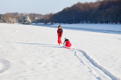 Mother and daughter in snowy winter park. Middle aged women pulling red sledge with her daughter across a snow field Royalty Free Stock Photography