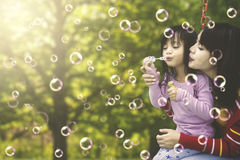 Mother and daughter with soap bubbles outdoors Stock Photo