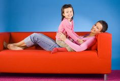 Mother and daughter on the sofa stock images