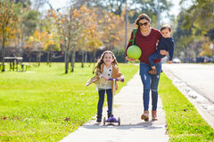 Mother daughter and son family in the park. Walking with ball and skate scooter Royalty Free Stock Images