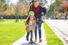 Mother daughter and son family in the park. Walking with ball and skate scooter Royalty Free Stock Photo