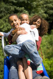 Mother, daughter and son on playground slide Royalty Free Stock Image