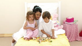 Mother, daughter and son playing with toy cubes on the bed Stock Image