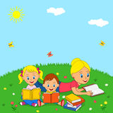 Mother, daughter and son reading books on a green meadow Stock Photo
