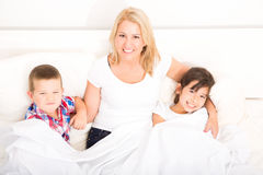 Mother with daughter and son relaxing in bed Stock Images