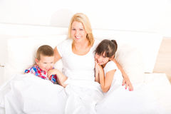 Mother with daughter and son relaxing in bed Royalty Free Stock Image