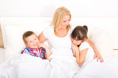 Mother with daughter and son relaxing in bed Royalty Free Stock Photos