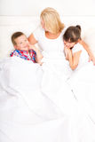 Mother with daughter and son relaxing in bed Stock Photos