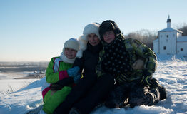 Mother with daughter and son sitting on snow in winter Royalty Free Stock Photos