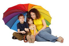 Mother, daughter and son with umbrella sitting Stock Photos