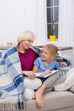 Mother and daughter spending time together, reading fairy tales. Little girl staying at home with her mom during illness Stock Image