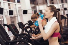 Mother and daughter drinking water on treadmill in gym. They look happy, fashionable and fit. royalty free stock photo
