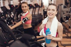 Mother and daughter drinking water on treadmill in gym. They look happy, fashionable and fit. royalty free stock photos