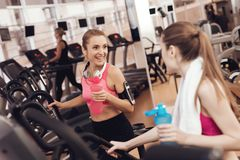 Mother and daughter drinking water on treadmill in gym. They look happy, fashionable and fit. stock photos
