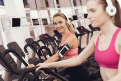 Mother and daughter running on treadmill at the gym. They look happy, fashionable and fit. Mother and daughter in sportswear running on treadmill at the gym Stock Photos